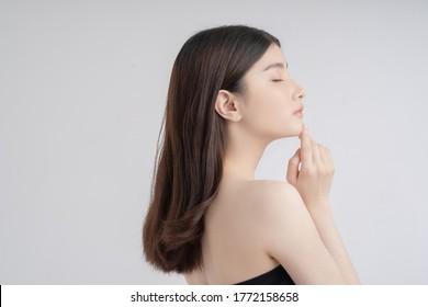 Schöne asiatische Frau mit schönem Gesicht. Seitenansicht. Sie berührt ihr Kinn
