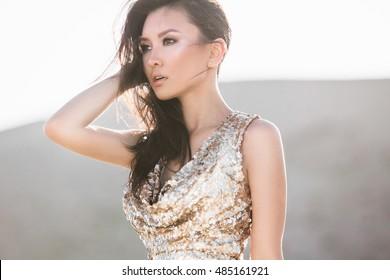 Schöne asiatische Frau in der Mode luxuriöse glänzende Kleidung in der Wüste