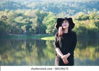A beautiful asian woman with feeling happy and smiley face in garden nature mountain and blue sky