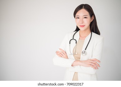 Beautiful asian woman female doctor crossed arm with smile isolated on white background. Metaphor to medical, healthcare, doctor, clinical, checkup, hospital concept.