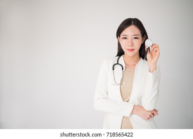 Beautiful asian woman female doctor holding stethoscope isolated on white background. Metaphor to medical, healthcare, doctor, clinical, checkup, hospital concept.