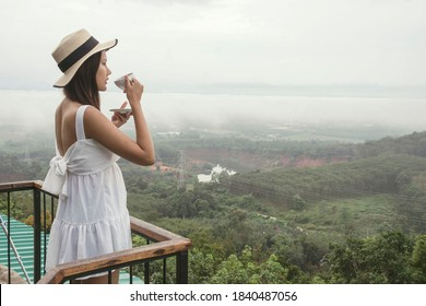 A beautiful Asian woman gets up in the morning drinking coffee on the top of the mountain, enjoying the view in the fog.