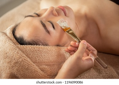 Beautiful Asian Woman getting facial nourishing at spa salon. Masseuse hands doing Face Massage. treatment, skincare, Facial Cleansing, Moisturizer.