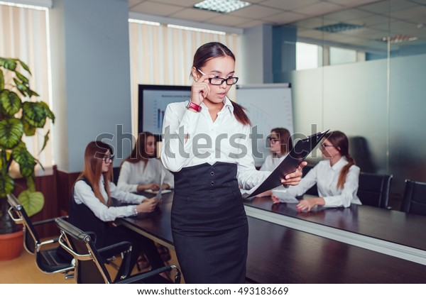 Beautiful asian woman in glasses standing on the background of business people with documents in hand