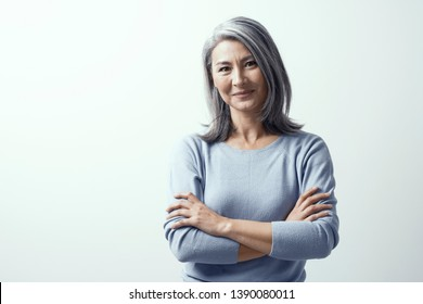 Beautiful Asian Woman with Grey Hair and Dark Skin Stands on a White Background in Studio Smiling Kindly. Head Tilted, Hands Crossed