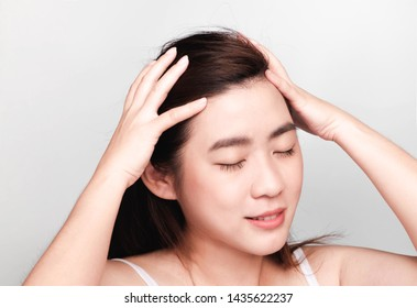 Beautiful Asian woman, hand hold soft hair. Close your eyes, relax, comfortably. Concepts about scalp care products.