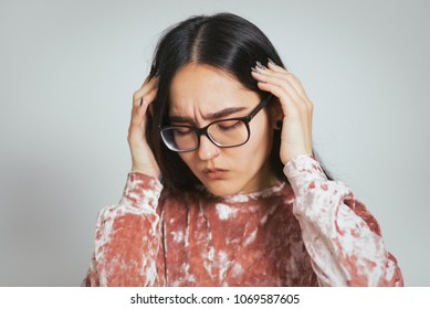 beautiful asian woman has migraine, headache, wears glasses and pink sweater, studio photo on background