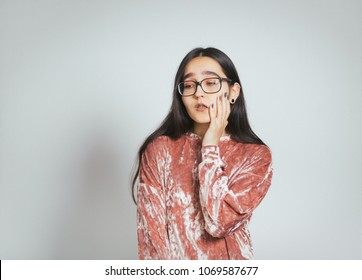 beautiful asian woman has toothache, headache, wears glasses and pink sweater, studio photo on background