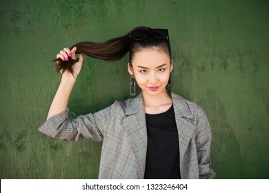 Beautiful asian woman having fun and hold her hair in hand smiling