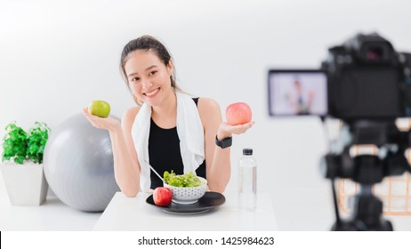 Beautiful asian woman healthy blogger is showing apple fruite and clean diet food. In front of the camera to recording vlog video live streaming at home.Fitness influencer on social media online.