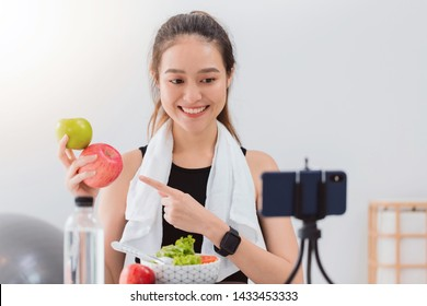 Beautiful asian woman healthy blogger is showing apple fruite and clean diet food. In front of the smartphone to recording vlog video live streaming at home.Fitness influencer on social media online.