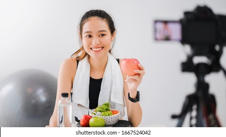Beautiful asian woman healthy blogger is showing fruit and clean diet food. In front of the camera to recording vlog video live streaming at home.Fitness influencer on social media online.
