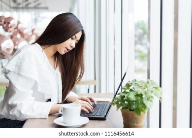 Beautiful Asian woman hipster using laptop computer at coffee cafe. Young attractive businesswoman working outdoor office in cafe.