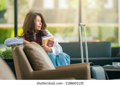Beautiful Asian woman holding book and Passport, waiting for flight at airport, travel or study abroad concept, with copy space.
