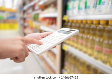 A beautiful Asian woman holding a calculator to calculate the cost and price reduction in a supermarket. Concept of price reduction, saving and value
