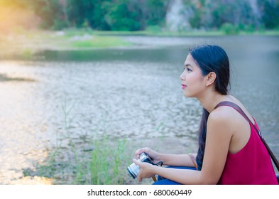 Beautiful Asian woman holding camera Sitting by the pool watching sunset