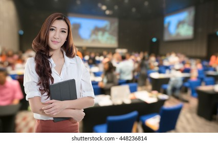Beautiful asian woman holding document on the Abstract blurred photo of conference hall or seminar room with attendee background.