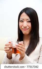 beautiful asian woman holding a glass of tea