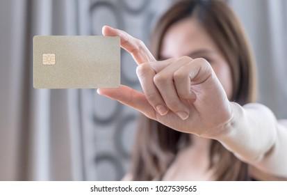 Beautiful Asian woman holding golden blank credit card