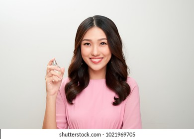Beautiful asian woman holding a perfume bottle and applying it