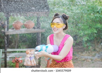 Beautiful Asian woman holding plastic water gun in Traditional Costume of Thailand playing water in Songkran festival