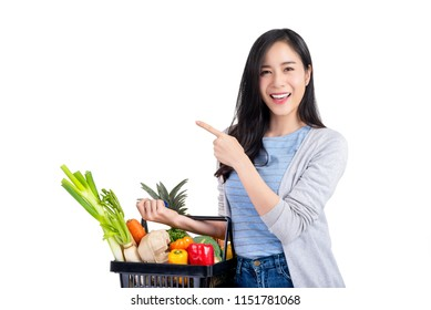 Beautiful Asian woman holding shopping basket full of vegetables and groceries, studio shot isolated on white background