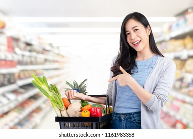Beautiful Asian woman holding shopping basket full of vegetables and groceries in supermarket