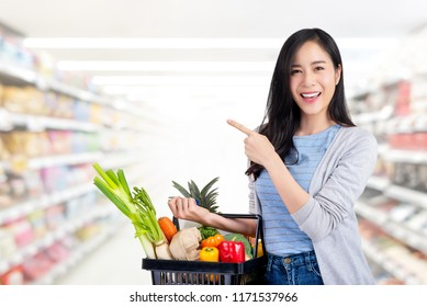 Beautiful Asian woman holding shopping basket full of vegetables and groceries in supermarket pointing to empty space aside