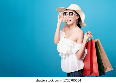 Beautiful asian woman are holding shopping bags with face happily in blue seamless,isolated background. Shopping lifestyle, online shopping concept.
