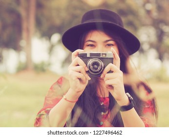 Beautiful Asian woman holding vintage camera,she's talking a photo in the park.