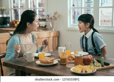 Beautiful asian woman housewife with bad little girl daughter screaming at each other. Concept of family conflict. angry mom and kid in uniform argue in breakfast time in morning before school.