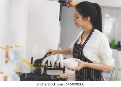Beautiful asian woman or housewife is cooking food for family in white kitchen
