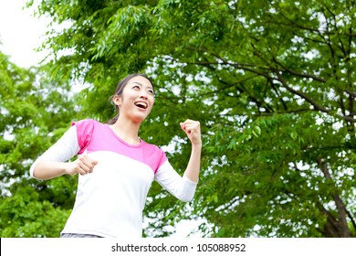 a beautiful asian woman jogging in the park