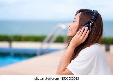 A beautiful asian woman listening to music with headphone while sitting by swimming pool