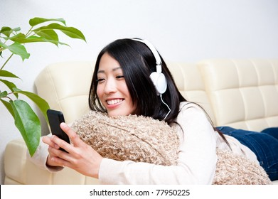 beautiful asian woman listening to music by smartphone