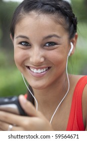 Beautiful Asian woman listens to music on a portable player. She is smiling into the camera outdoors. Vertical shot.
