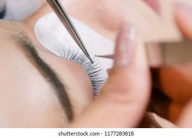 Beautiful Asian woman with long eyelashes in a beauty salon during eyelash extension. Eyelash extension procedure. Eyelashes close up.