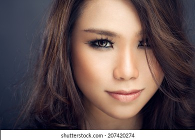 Beautiful Asian woman looking directly at camera - hair is covering one half of her face.