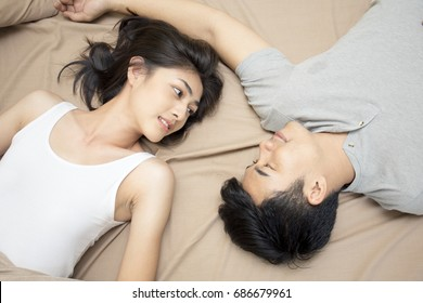 Beautiful asian woman looking man in bed, woman and man in love concept, 20s age