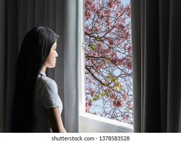 A beautiful Asian woman is looking out the window in the view as a flower.