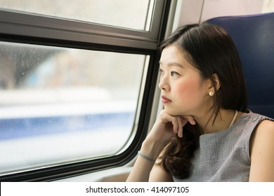 Beautiful asian woman looking out of train window, with copy space