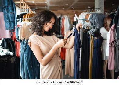 ファッションストレードのドレスを買い物する際に、価格札を見る美しいアジア人女性