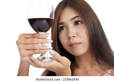 Beautiful Asian woman looking at  red wine  isolated on white background