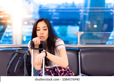 Beautiful asian woman looks at wristwatch for checking the time. Gorgeous girl feels boring the delays flight. Lovely beautiful woman is waiting for long time. She sits on chair at airport. copy space
