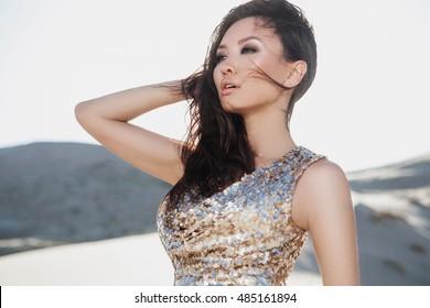 Schöne asiatische Frau in luxuriösem Modekleid in der Wüste