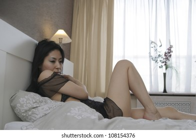 Beautiful asian woman lying on her bed