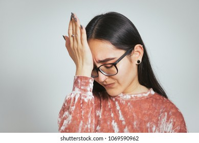 beautiful asian woman made a mistake wearing glasses and pink sweater, studio photo on background