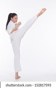 Beautiful asian woman makes kick in kimono on white