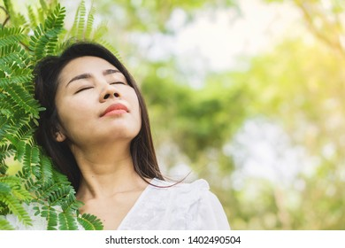 beautiful Asian woman with nature background enjoying fresh air under the tree in a park