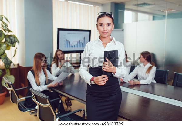 Beautiful asian woman on the background of business people with documents in hand
